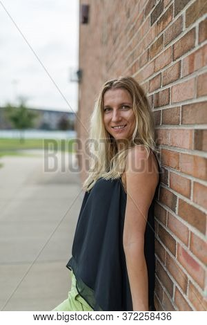 Portrait Of A Woman Looking At The Camera As She Leans Against A Brick Wall