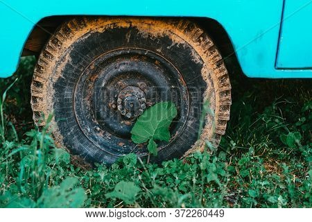 An Old Car With A Rusty Wheel Stands On The Grass