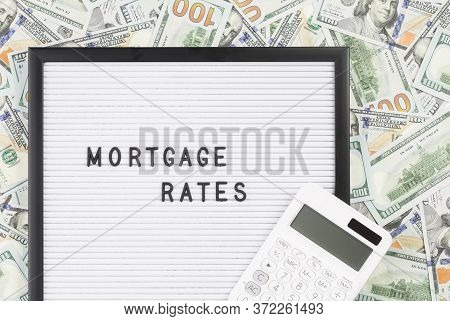 Mortgage Rates Text On Letter Board With Lots Of Hundred Dollar Bills As Background. Mortgage Intere
