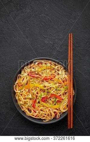 Chilli Garlic Hakka Noodles In Black Bowl On Dark Slate Tabpe Top. Indo-chinese Vegetarian Cuisine D