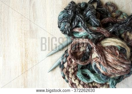 Multycolored Brown Turquoise Thread Clew Ball, Knitting Needles And Knitted Fabric On White Bleached