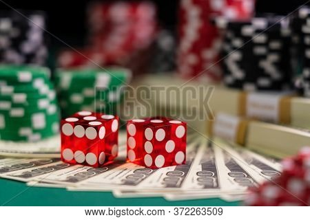 Casino red Craps dice with USD 100 bills - Shallow depth of field