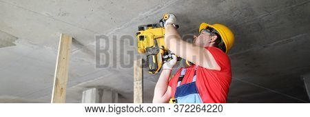 Builder Works With Special Equipment On Ceiling. Builder Helmet Holds Heavy Tool. Builder Works Punc