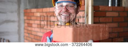 Happy Builder Holds Brick For Masonry And Smiles. Red Brick Masonry. Calculation Amount Necessary Bu