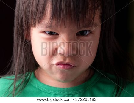 Portrait Face Of Asian Little Child Girl With Angry Expression On Dark Background.