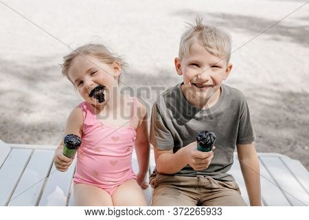 Boy And Girl Dirty Because Of Black Ice Cream. The Grimy Faces Of Children. Brother And Sister Eat U