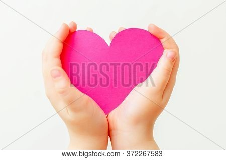 Closeup Of Paper Heart In Little Hands Of Child On White Background. Pink Heart In Hands On White.