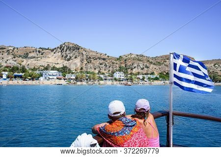 Young Couple Look At Stegna Beach From Prow Of Tourist Boat. Next To Them Greek Flag. (rhodes, Greec