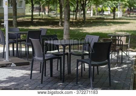 Empty Area Of A Summer Cafe. Tables And Chairs Unoccupied By Visitors. Sunny Summer Day Without Peop