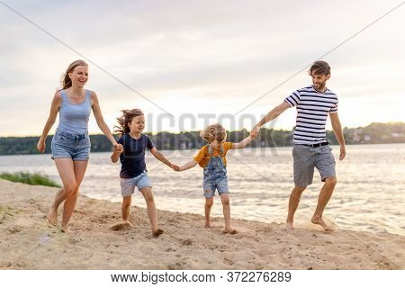 Shot of a family of four spending the day at the beach