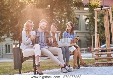 young caucasian businesspeople laughing at bench in a park with their cell phones, laptop, tablet. Looking at camera, eye contact. Break, pause from work.
