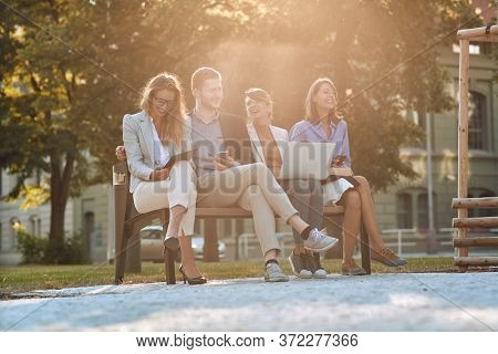 group of young businesspeople laughing at bench in a park with their cell phones, laptop, tablet. Break, pause from work.