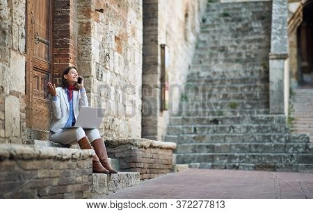 beautiful young female talking on her cell phone with laptop, sitting outdoor on stairways in italy