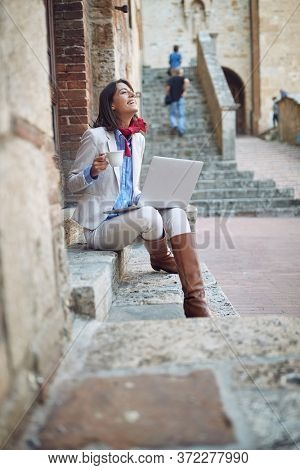 beautiful young female sitting on stairways drinking coffee outside with her head up, smiling,  enjoying,