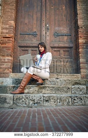 beautiful young female sitting on stairways drinking coffee outdoor, looking at laptop