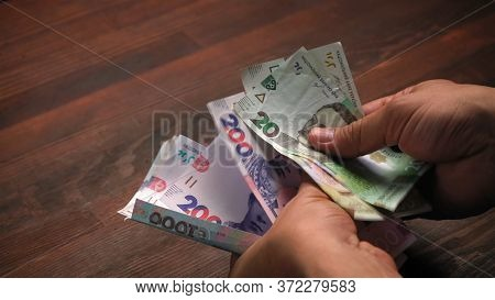 Ukrainian Man Holds Paper Hryvnia, Saving Money For Retirement. Cost Of Living Concept. Inflation Co
