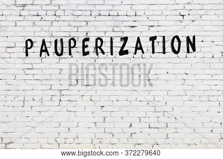 White Brick Wall With Inscription Pauperization Handwritten With Black Paint