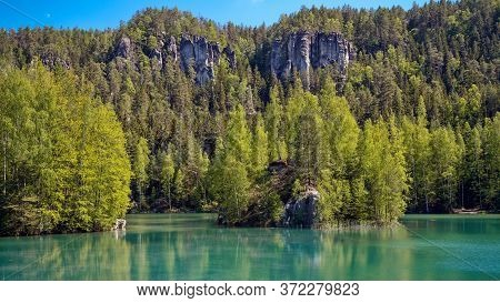 Beautiful View On Clear Cyan Lake With Mighty Rocks In Colorful Yellow Green Forest In The Backgroun