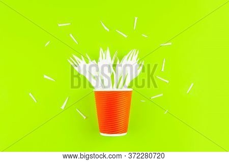 Broken Plastic Forks In A Plastic Cup Instead Of A Bouquet Of Flowers On A Green Background.the Conc