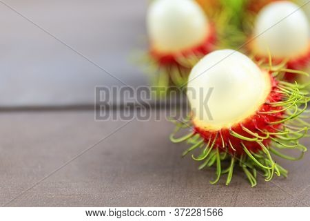 Close Up Fresh Rambutan Peeled On Wood Table With Blur Rambutan Peeled Background. Tropical Fruit Fr