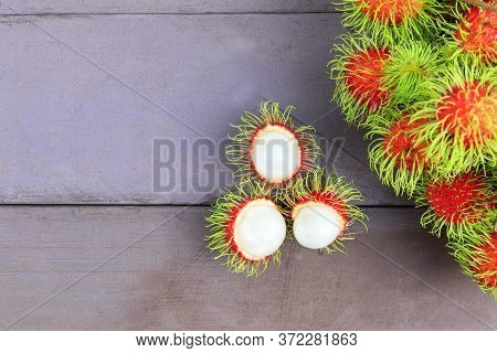 Top View Fresh Rambutan Peeled On Wood Table With Bunch Of Fresh Ripe Rambutan Background. Tropical