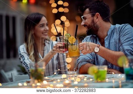 Young lovely couple making a toast at night party
