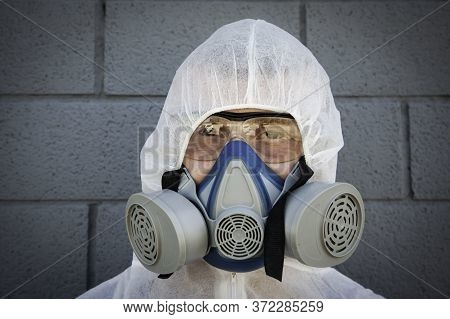 Man In Protective Clothing And A Gas Mask On An Urban Gray Background - Worker Ready For Disinfectio