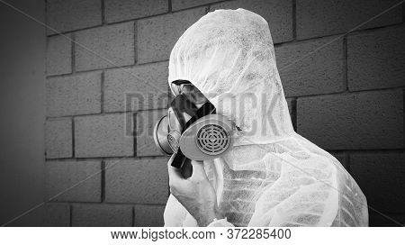 Man In Protective Clothing And A Gas Mask On An Urban Gray Background - Worker During Disinfection A