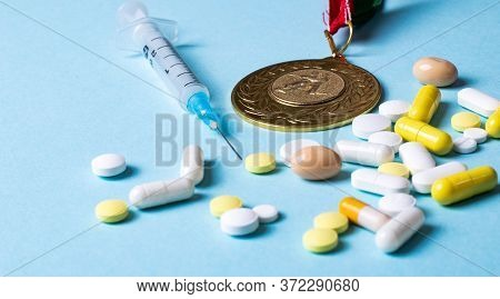 Syringe, Medals And Pills On A Blue Background. Doping In Sports. Abuse Of Anabolic Steroids For Spo