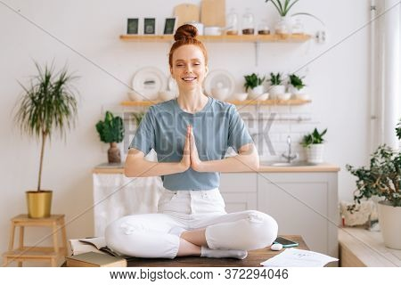 Portrait Of Beautiful Peaceful Meditating Redhead Young Woman Is Putting Her Hands Together On Chest