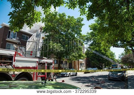 MONTREAL, CANADA - JUNE 18, 2020:  Firefighters climb skywards to tackle a blaze in a residential building in Montreal in Canada