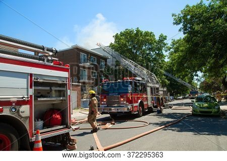 MONTREAL, CANADA - JUNE 18, 2020:  Firefighters and firetruck ready to tackle a blaze in a residential building in Montreal.