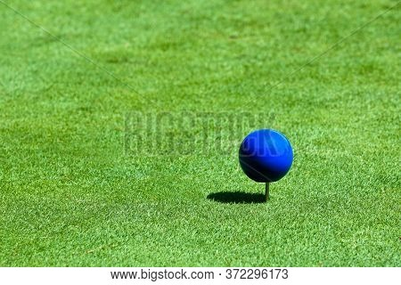 A Close Up View Of A Blue Tee Marker On A Golf Course On A Sunny Day. N.