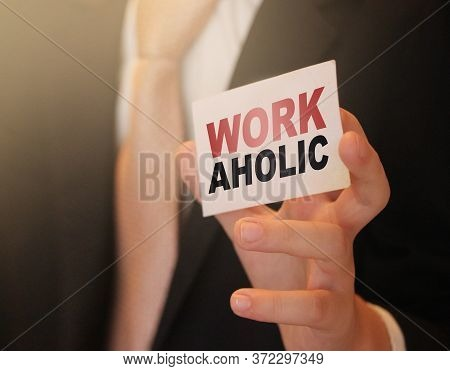 Workaholic Word On A Card In Hand Of Businessman. Devoted To Business Or Career Concept