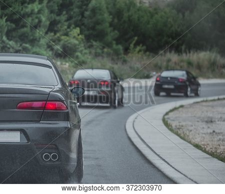 Multiple Cars Driving Together In A Column On A Cold Rainy Day. Car Enthusiast Gathered And Going Fo