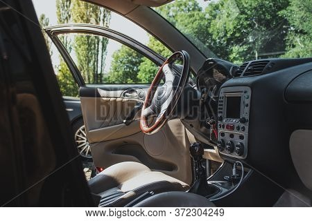 Wide Interior Of An Old Italian Hatchback. Wooden Steering Wheel On A Sunny Day, Doors Opened Lettin