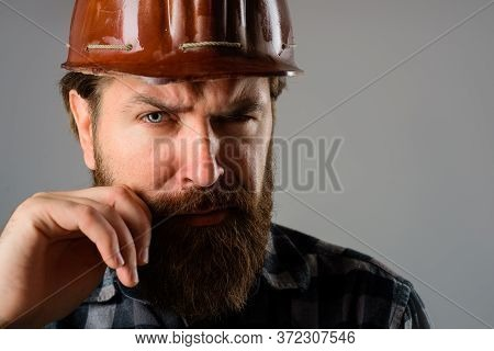 Serious Workman In Hard Hat. Builder Concept. Building, Industry, Technology. Bearded Builder In Har