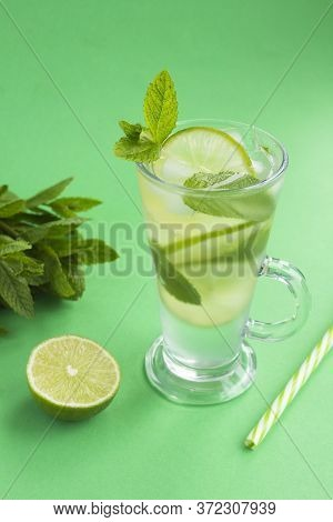 Infused Water Or Cold Lemonade With Lime, Ice And  Mint  In The Glass  On The Green Background. Loca