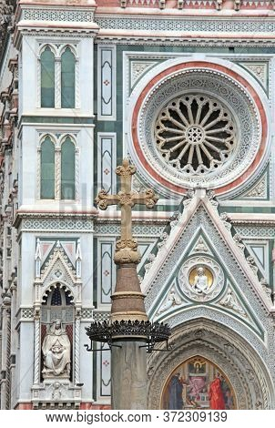 Detail Of Giotto's Bell Tower In Florence In Italy And The Cross In The Foreground