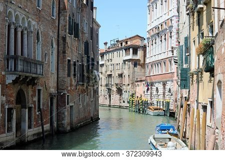 Characteristic View Of The Island Of Venice In Italy With The Navigable Canal And Moored Boats