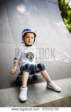 Boy With A Skate In A Skate Park. The Boy Learns To Skate, In Full Protection.