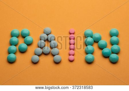 Word Pain On Orange Background Written With Colorful Pills. Painkiller Tablets Taken By Prescription