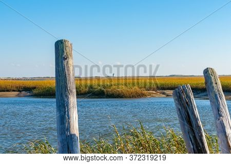 Salt Marsh And Long Point Lighthouse In Distance On Horizon Near Provincetown Cape Cod, Usa.