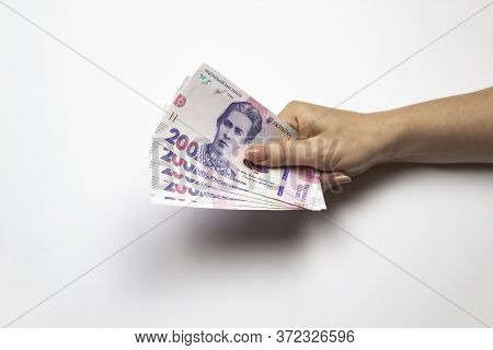 Female Hand Holds A Thousand Hryvnia. Ukrainian Currency With Woman's Hand Against A White Backgroun