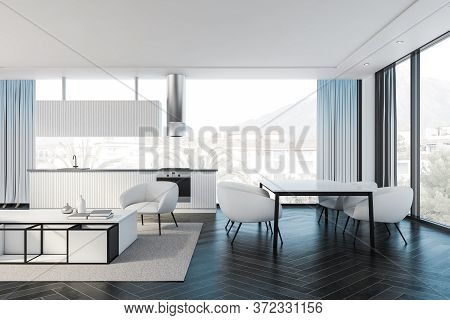 Interior Of Modern Kitchen And Dining Room With White Walls, Black Wooden Floor, White Countertops A
