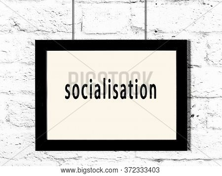 Black Wooden Frame With Inscription Socialisation Hanging On White Brick Wall