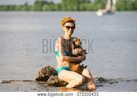 Mature Caucasian Woman Sits In Water On Stone And Hold Dog Of Dachshund Breed In Arms. Theme Heat An