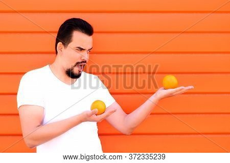 Smiling Man Posing Like Martial Arts Fighter Holding Two Juicy Oranges On Palms With Funny Face. Abs