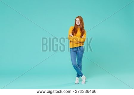 Smiling Young Redhead Woman Girl In Yellow Knitted Sweater Posing Isolated On Blue Turquoise Backgro