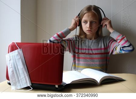 A Blonde Preteen Girl With Headphones Sits At The Table With A Computer And A Book. Distance Educati
